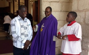 Rev. Garth Minott (centre) greets a member following Service at the UWI Chapel. His younger son, Stephen, is at right.