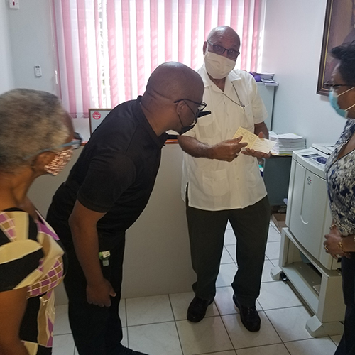 Archbishop Gregory shows his Vaccination Certificate to Miss Beverley Newell, Communication Officer; Rev. Craig Mears, Director of Youth Ministries and Mrs. Jacqueline Mighty, Diocesan Secretary.